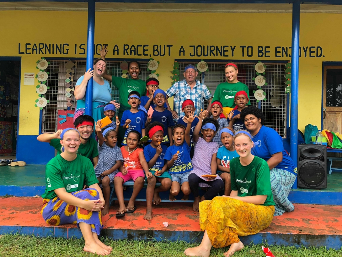 High school volunteers and children before a sports day in Fiji during their teen volunteer abroad program.